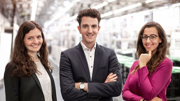 Three Schaeffler employees and young talents in portrait in a factory hall.