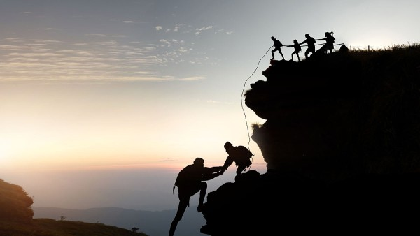 Through cooperation and cohesion people climb a mountain together, that is symbolic for a new goal.